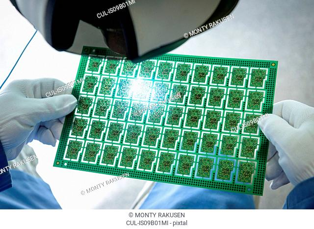 Worker inspecting circuit boards in circuit board assembly factory, close up