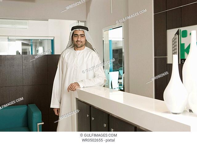 Man standing at reception desk, portrait