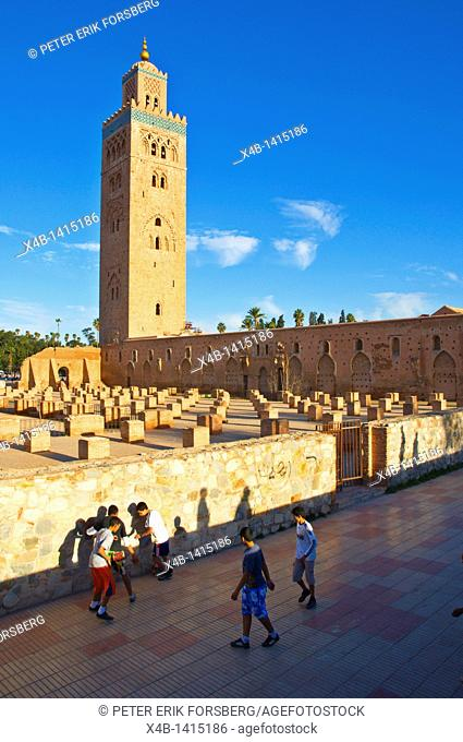 Boys playing football outside Koutoubia mosque Marrakesh central Morocco Africa