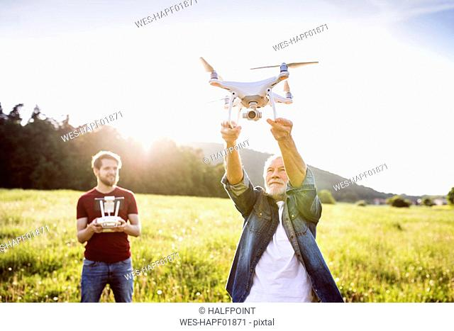 Senior father and his adult son with drone on a meadow