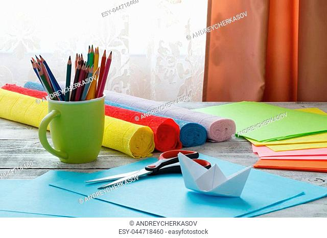 Set of origami boats and square sheets of colored paper on a wooden table. How to make a simple origami ship. Paper folding tutorial