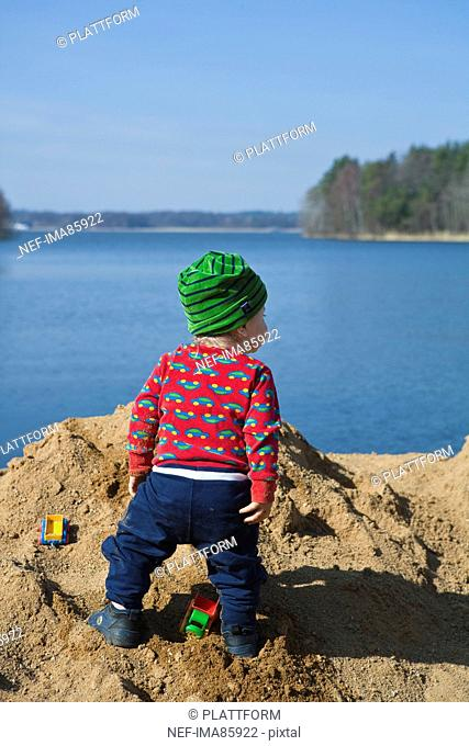 Baby boy standing on beach