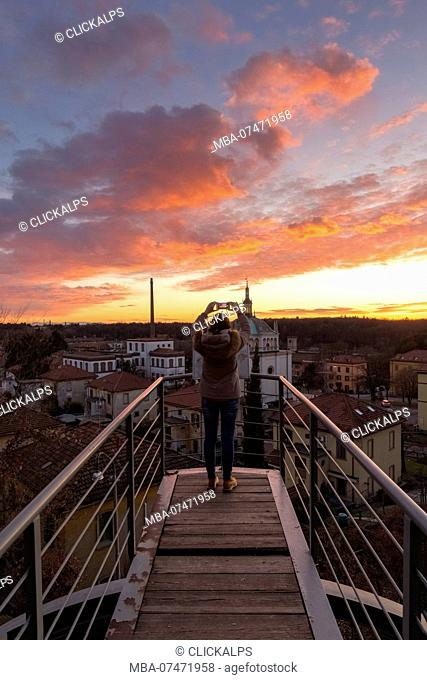A turist taking a picture during a sunset at the balcony over the model worker village of Crespi d'Adda, Unesco World Heritage Site