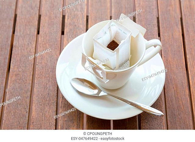 White coffee cup and spoon with white pre-packaged blended coffee in paper filter set on wooded table