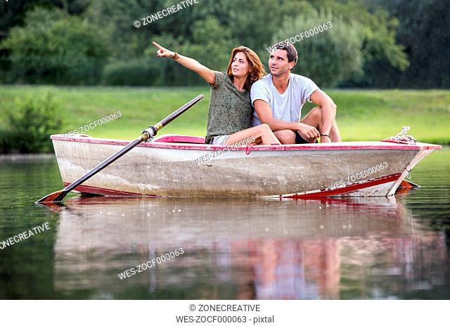 Young couple sitting in a rowing boat on lake looking at distance