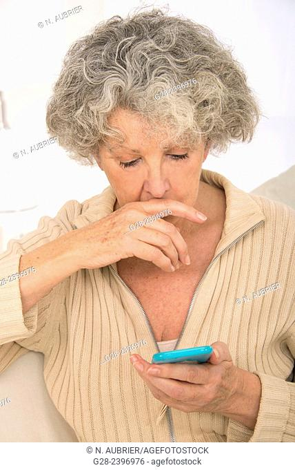 Puzzled beautiful senior woman writing and reading a message on her mobile-phone, at home