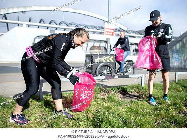 24 March 2019, Lower Saxony, Hannover: The joggers Nicole (l) and Oliver collect garbage lying on the ground around the Noltemeyer Bridge in the Bothfeld...