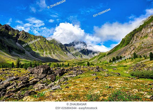 Mountain valley and peak in clouds . Eastern Sayan . Russia