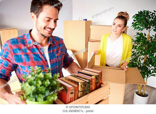 Young couple moving home, packing belongings into cardboard boxes