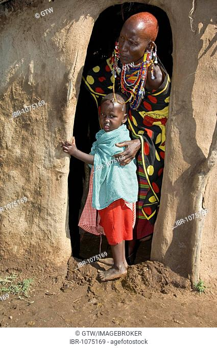 Masai mother and her child at the entrance to a hut, Masai Mara, Kenya, East Africa