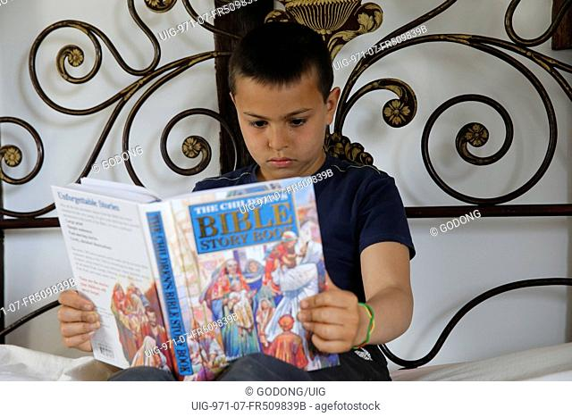 10-year-old boy reading a Bible