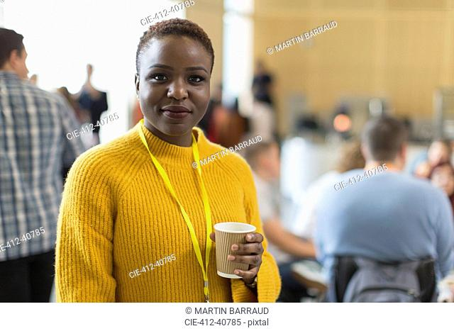 Portrait confident businesswoman drinking coffee at conference