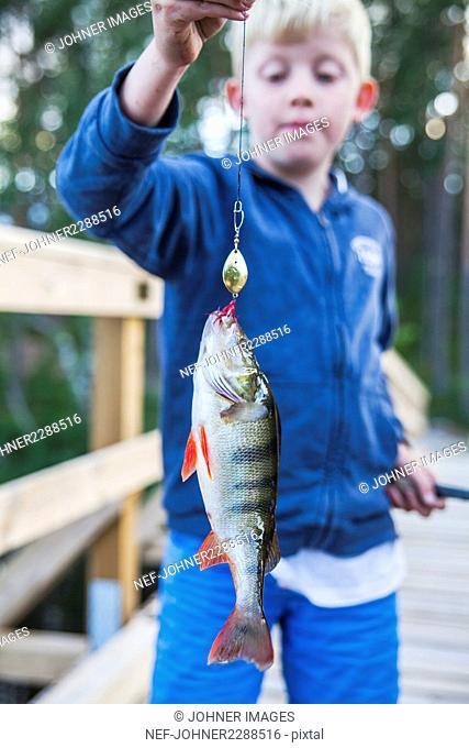 Boy holding caught fish