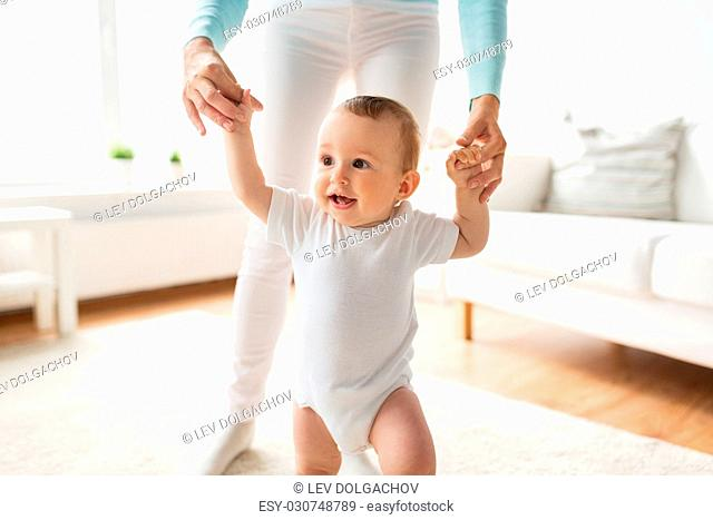 family, child, childhood and parenthood concept - happy little baby learning to walk with mother help at home