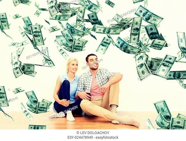 home, people, moving, finances and real estate concept - happy couple of man and woman sitting on floor and dreaming at new place over dollar money falling from...