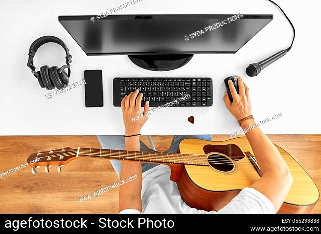 young man with computer and guitar at table