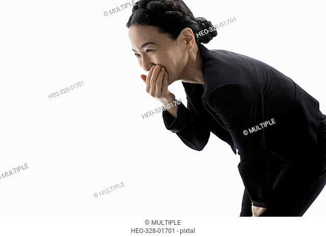 Laughing businesswoman bending, covering mouth against white background