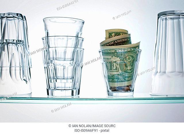 Dollar bills in glass on shelf