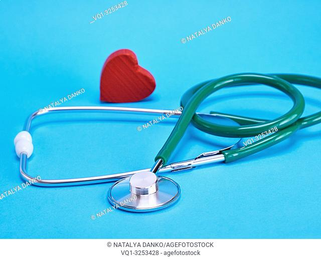 green medical stethoscope and red decorative heart on a blue background