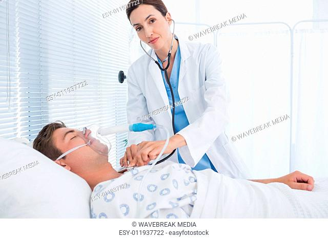 Smiling doctor auscultating her patients chest