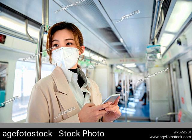 Wearing a mask of the young woman standing in the subway