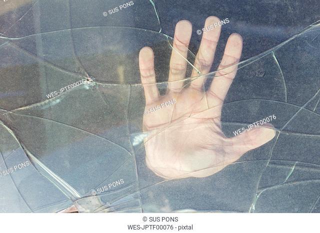 Hand of a young man behind broken windscreen on a scrapyard