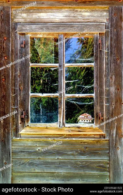Altes verwittertes Holzfenster mit Spinnweben in einem Bauernhaus; old weather-beaten wooden window with spider webs at a farm house