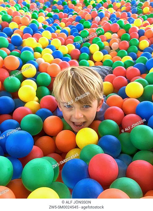Boy, 7 years old, playing in the ball pit on Braendesgardshaven playground on Bornholm, Denmark