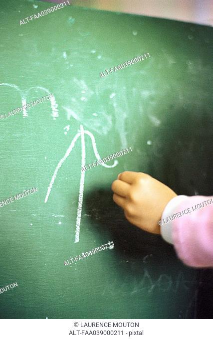 Child's hand writing on chalk board