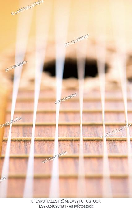 Macro shot of wooden acoustic guitar showing the neck and strings in extreme close up