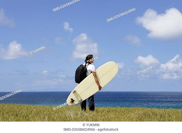 man holding surf board, looking out to sea