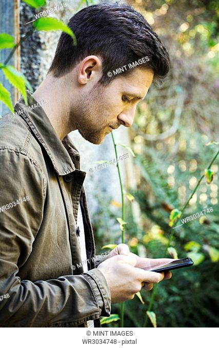 A young man in a brown jacket texting using a smart phone