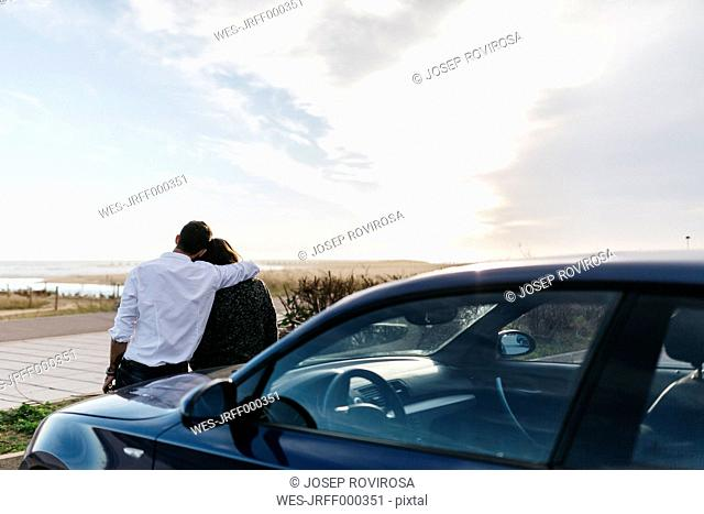 Spain, Cubelles, back view of a young couple sitting on the hood of the car watching the sea at sunset