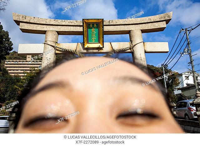 Woman praying and torii of Toshogu Shrine, Hiroshima, Japan