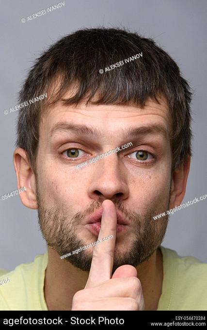 Portrait of a man of European appearance who put a finger to his mouth, gesture of silence, close-up