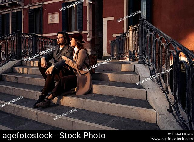 Young couple sitting on a bridge in the city of Venice, Italy
