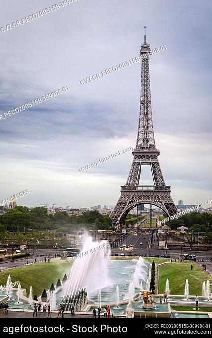 Eiffel tower on Paris with a gray sky and a fountain in front