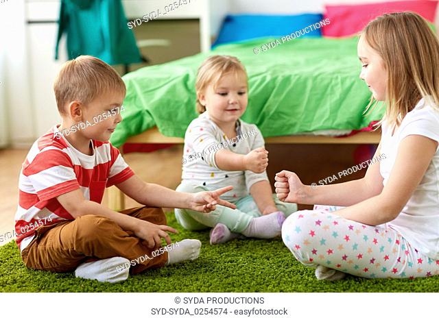 kids playing rock-paper-scissors game at home