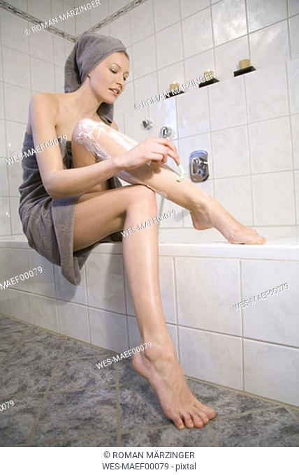Young woman shaving legs, low angle view