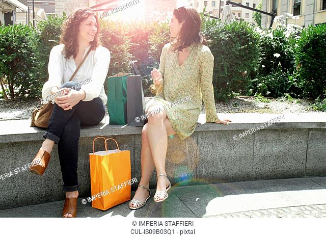 Two women with shopping bags sitting on wall chatting, Milan, Italy