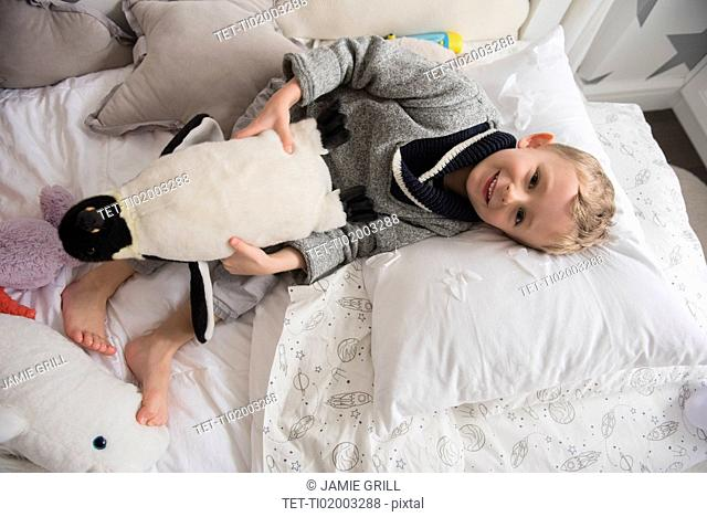 Little boy (4-5) lying in bed with toy in hands