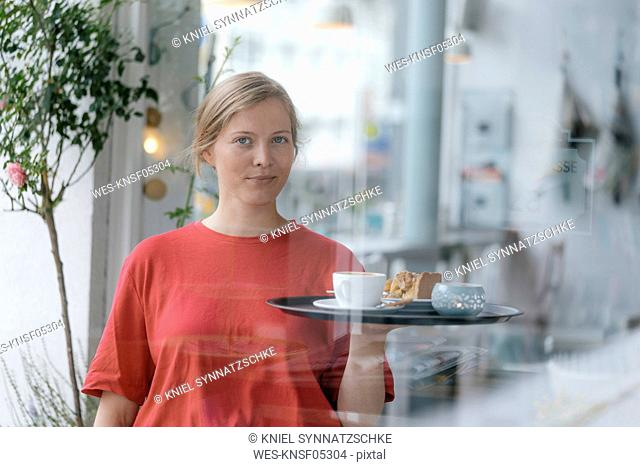 Portrait of young woman serving coffee and cake in a cafe