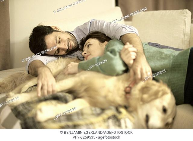 couple with dog laying on couch at home, in Munich, Germany