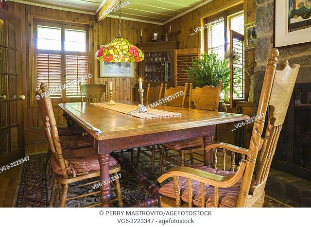 Antique wooden dining table with Czechoslovakia era made early Americana style wooden High-back chairs inside an old circa 1850 Canadiana cottage style home