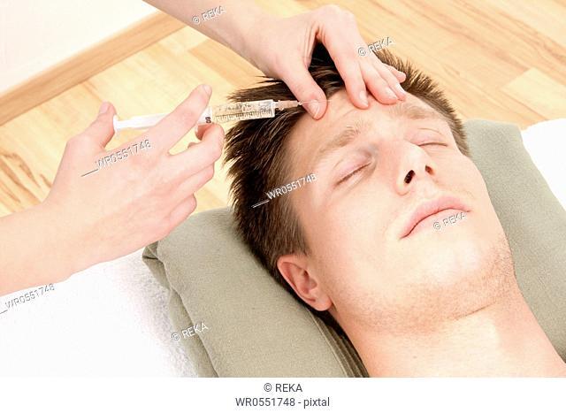 Woman injecting man botox