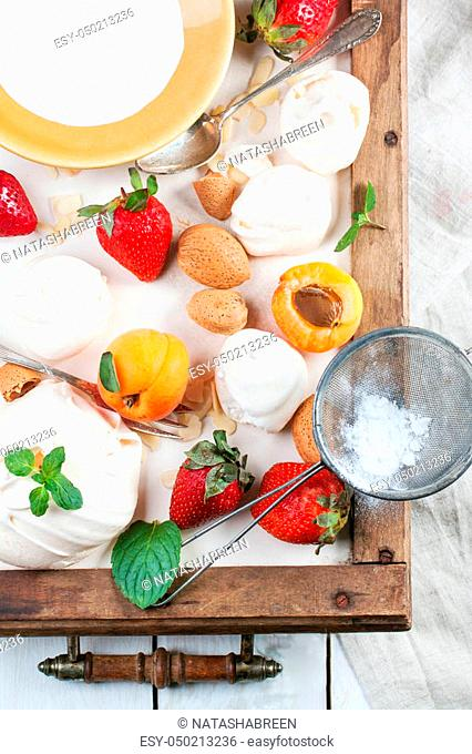 Homemade meringue with apricots, strawberries, almonds and cream. Ingredients for dessert Eton mess. Top view