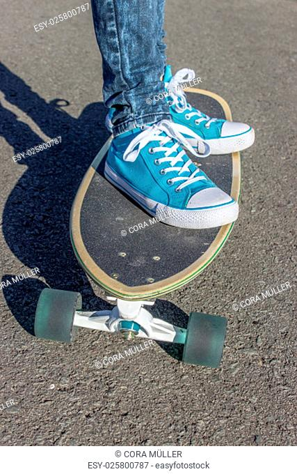Girl with blue shoes on a skateboard