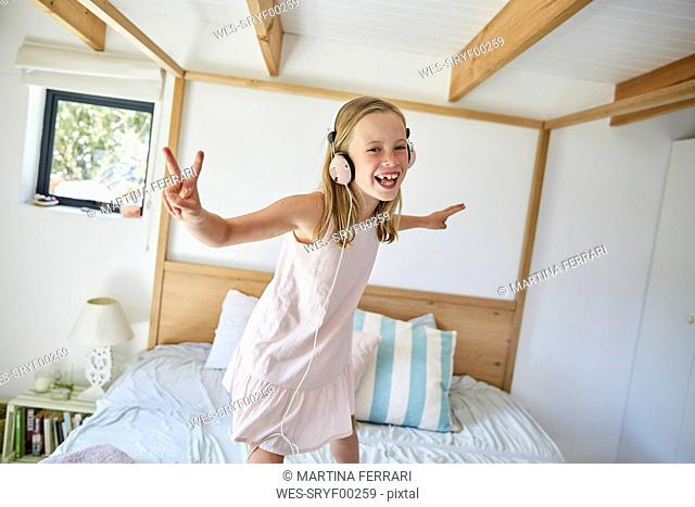 Portrait of smiling little girl dancing on bed at home while listening music with headphones