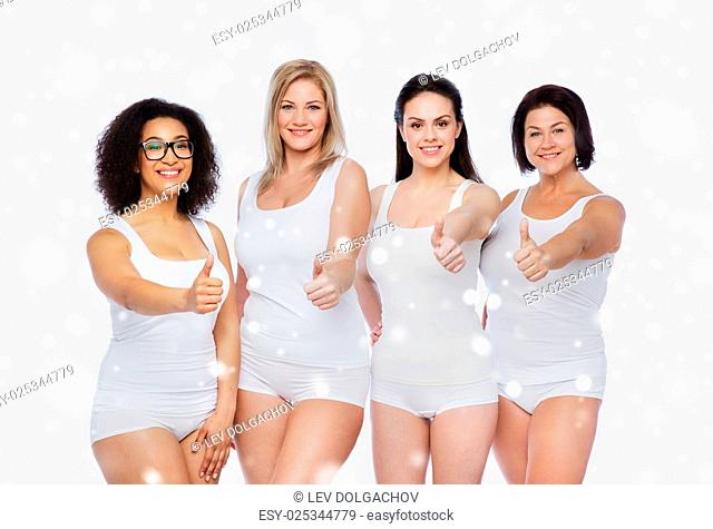 gesture, friendship, beauty, body positive and people concept - group of happy different women in white underwear showing thumbs up over snow