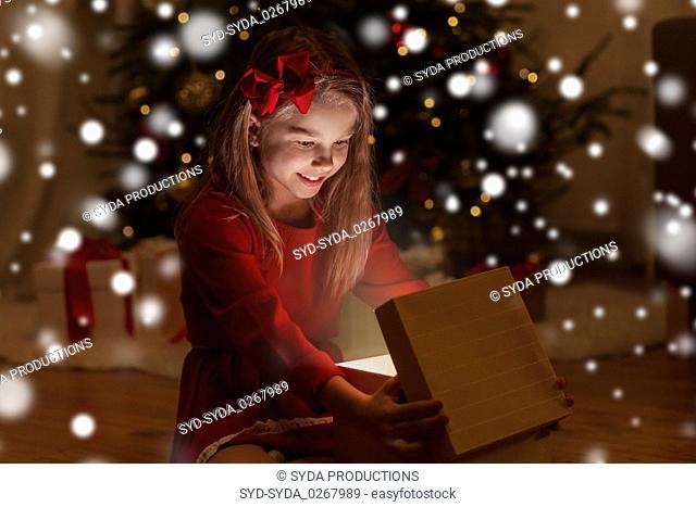 smiling girl opening christmas gift at night